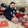 Veterans Day celebration at Tyngsboro Elementary School. Navy veteran Aaron Norton of Tyngsboro reads cards addressed to veterans with his son Lucas, 9, and daughter Caitlyn, 7.  (SUN/Julia Malakie)