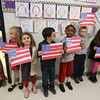 Veterans Day celebration at Tyngsboro Elementary School. Students line the halls for veterans' parade. From left: kindergarten students Molly Meyer, Ava Perry, Ava Izzo, Nicholas Monti, Alexis Makarutsa, Reese Wooster, Gabrielle Patenaude and Emily Wood. (SUN/Julia Malakie)