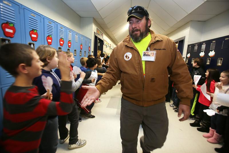 Veterans Day celebration at Tyngsboro Elementary School. Fourth grader Hunter Mosher, 9, left, greets Army veteran Ray Reekie of Tyngsboro as veterans parade through school. (SUN/Julia Malakie)