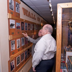 Curator Bill Chivalette points out to Harold Bost many of the famous former enlisted personnel  honored on the Wall of Achievers