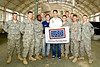 December 8, 2012-NASCAR drivers Joey Logano and Ricky Stenhouse, Jr. break away from the raceway to deliver holiday cheer to troops overseas on USO Tour. Logano (R) and Stenhouse pose for a photo with members of the Pennsylvania and south Carolina Army National Guard.