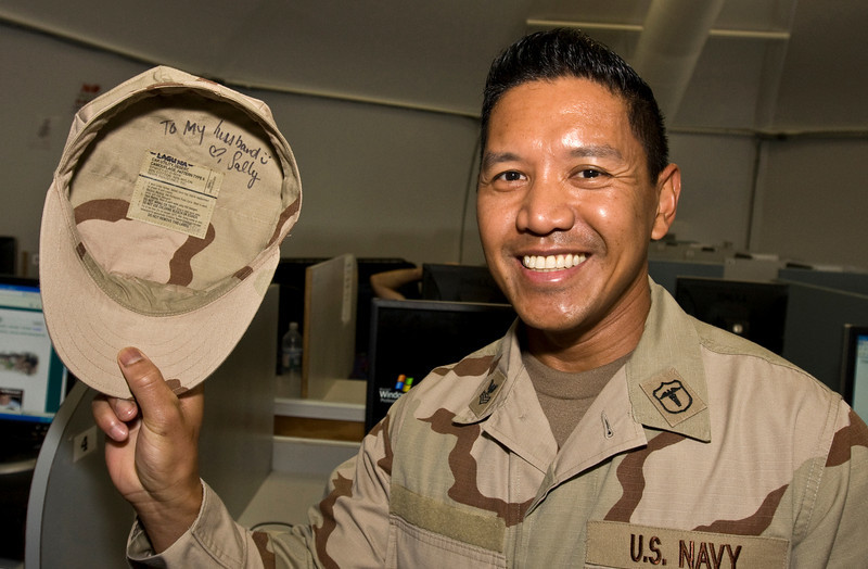 """A U. S. Navy Sailor shows off his hat signed by actress Sally Pressman of Lifetime's top-rated drama """"Army Wives"""" after he presented her the name tape off of his uniform at a meet and greet event at Camp America, Naval Station Guantanamo Bay, Cuba as part of USO/Armed Forces Entertainment tour December 12-16."""