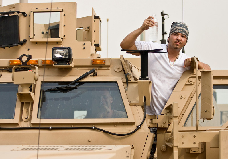 """Hip-Hop artist Ron """"Baby Bash"""" Bryant poses with a Soldier on an MRAP vehichle at Tallil Air Base, Iraq Sept. 8, 2008."""