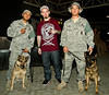 January 18. 2012. Grammy-nominated rapper, Paul Wall visits U. S. troops at an undisclosed military base in the middle east on his fifth USO Tour. Wall poses with U. S. Air Force Dog Handlers, Sr. Airman Stephen Rivera, 23, from San Antonio (Left) and his dog Ema and Staff Sgt. Leon Daniel, 25, of Victorville, CA and his dog, Mink.