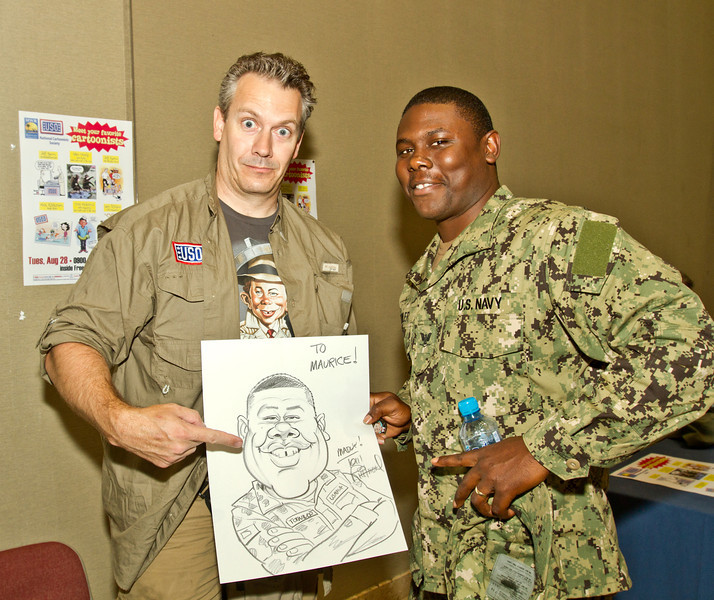 August 28, 2012-Undisclosed military base in the Middle-East. national Cartoonists Society members, Jeff Bacon, Dave Coverly, Jeff Keane, Rick Kirkman, Tom Richmond and Sam Viviano visted with military personell and booted their morale by talking with them and drawing cartoons and caracatures for them. Tom Richmond poses with the caricature he drew for U. S. Navy YN3 Maurice Tutwiler, 28, from Memphis, TN.