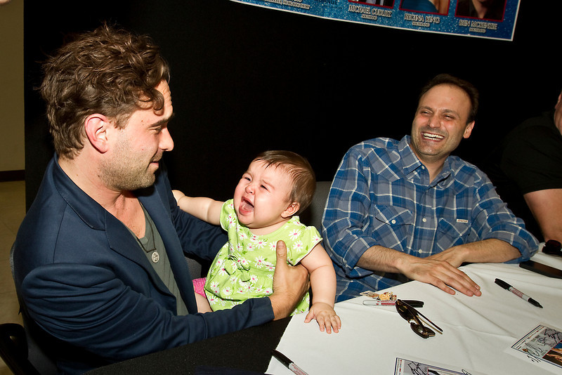 """May 5, 2012. Kadena Air Base, Okinawa, Japan. """"The Big Bang Theory's"""" Steven Molaro and Johnny Galecki join Michael Cudlitz, Regina King and Ben McKenzie of """"Southland"""" on a seven-day, spirit lifting USO Tour to Japan. Nami Whitener is not sure about Johnny Galecki of """"The Big Bang Theory"""". Nami is the daughter of U. S. Air Force Staff Sergeant John Whitener and his wife Ayumi. The Whiteners are from Salem, SC. Steven Molaro of """"The Big Bang Theory"""" laughs as Nami expresses her opinion of Galecki."""
