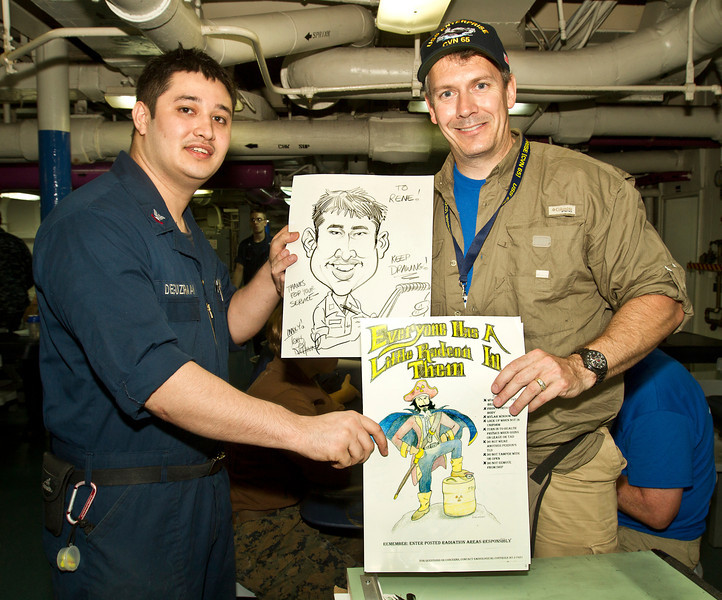 August 28, 2012-Undisclosed ship at sea. National Cartoonists Society members, Jeff Bacon, Dave Coverly, Jeff Keane, Rick Kirkman, Tom Richmond and Sam Viviano visit with military personell and boost their morale by talking with them and drawing cartoons and caracatures for them. U. S. Navy MM2 Rene Deguzrman, 24, from Crescent City, FL trades cartoons with Tom Richmond.
