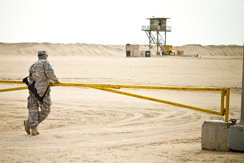 December 8, 2012-NASCAR drivers Joey Logano and Ricky Stenhouse, Jr. break away from the raceway to deliver holiday cheer to troops overseas on USO Tour. A lone Soldier mans his post at Camp Buering, Kuwait.