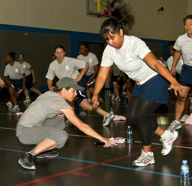 June 10, 2011. At an undisclosed military base in the Middle East. Health and Wellness expert Jillian Michaels and Fitness Guru Marco Borges lead boot camp style work out sessions while actress/media personality Celines Toribio adds excitement.Michaels gives personal attention to a participant. USO photo by Mike Clifton.
