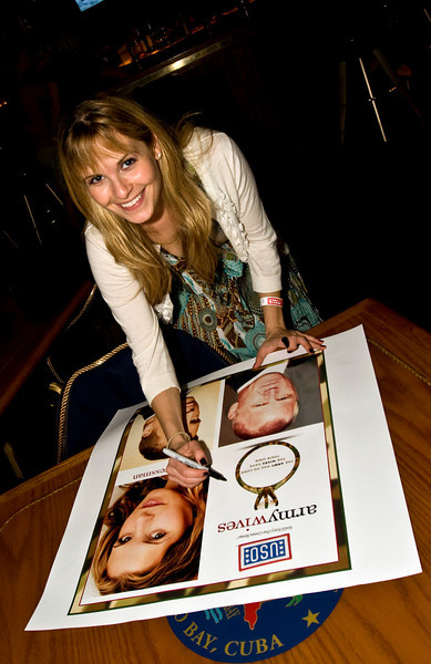 "Actress Sally Pressman of Lifetime's top-rated drama ""Army Wives"" autographs a poster at Rick's Lounge in Guantanamo Bay, Cuba as part of USO/Armed Forces Entertainment tour December 12-16."