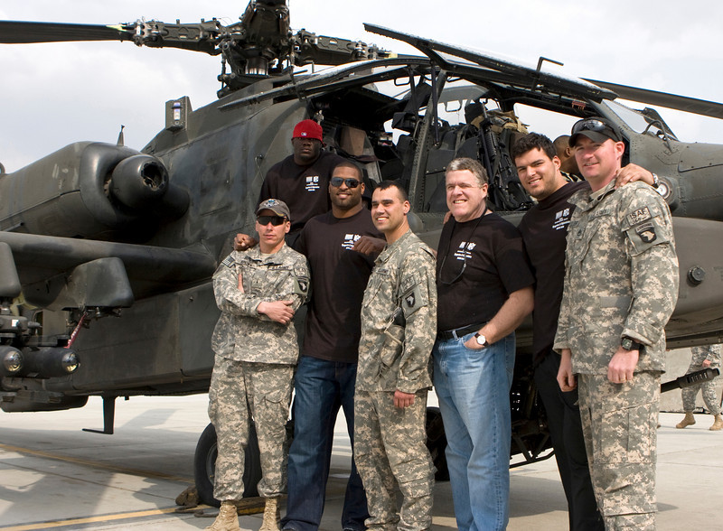 NFL players Tommie Harris of the Chicago Bears, Mike Rucker of the Carolina Panthers and Luis Castillo of the San Diego Chargers pose with Soldiers in front of an AH-64 helocopter while on the USO's Khyrgzstan and Afghanistan National Football League Tour March 2-10, 2008.