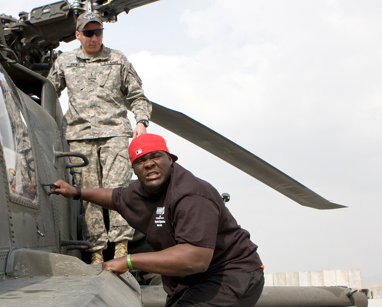 Tommie Harris of the Chicago Bears acts funny as he gets off of a U. S. AH-64 helicopter at Bagram Air Base while on the USO's Khyrgzstan and Afghanistan National Football League Tour March 2-10, 2008.