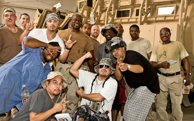 """Hip-Hop artist Ron """"Baby Bash"""" Bryant, along with Los Angeles morning show hosts Kurt """"Big Boy"""" Alexander and Emmanuel """"DJ Eman"""" Coquina pose with Soldiers, Sailors, Marines and Airmen at Tallil Air Base, Iraq, Sept. 8, 2008."""