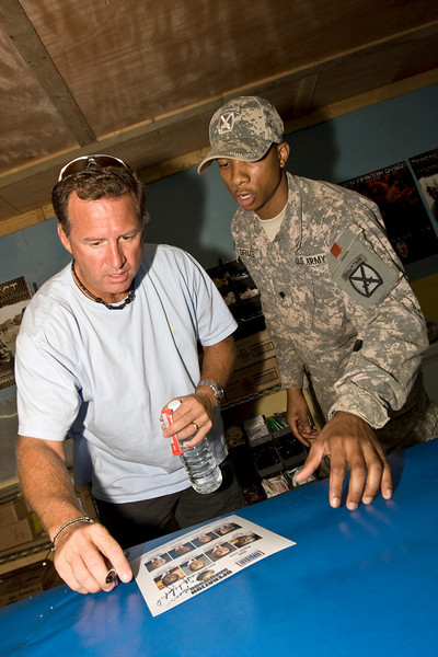 Mark Gottfried, former University of Alabama Head Coach signs an autograph. USO Operation Hardwood VI.