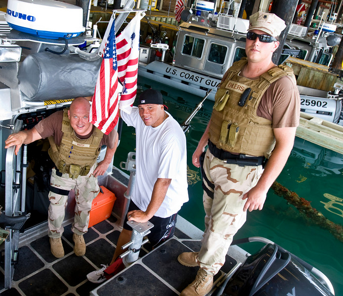 USO NFL Tour To Guantanamo Bay, Cuba June 26-29, 2009. Billy Miller inspects a U. S. Coast Guard Viper boat with members of MSST (Maritime Safety And Security Team) 91101 from Seattle, WA. He is pictured with BM2 Thomas Marsh (L) and MK2 Dylan Ehlers.