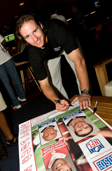 USO NFL Tour To Guantanamo Bay, Cuba June 26-29, 2009. Drew Brees autographs a poster.