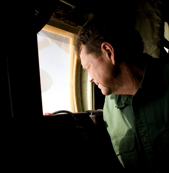 Tom Watson looks out the window of a U. S. Marine Corps C-130 at the barren terrain of Iraq.