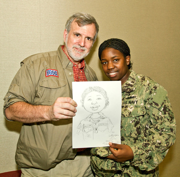 August 28, 2012-Undisclosed military base in the Middle-East. national Cartoonists Society members, Jeff Bacon, Dave Coverly, Jeff Keane, Rick Kirkman, Tom Richmond and Sam Viviano visited with military personell and booted their morale by talking with them and drawing cartoons and caracatures for them. Sam Viviano poses with U. S. Navy Petty Officer 3rd Class Lakera Williams, 26, from Birmingham, AL while she shows off the caricature Viviano drew for her.
