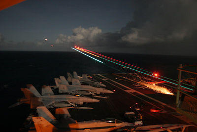 An F/A-18 Superhornet leaves streaks of light and a shower of sparks as it lands on the flightdeck of USS Ronald Reagan (CVN-76) during night flight-ops.  A 5-second shutter shows its progress from about 1/8-mile out until the moment the tailhook strikes the deck and pulls the arresting wire.