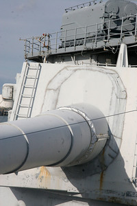 "TURRET PROTECTION - A close up of one of the three 16-inch guns within IOWA's aft Turret No. 3. The blast bags or ""bucklers/bloomers"" have been removed, with a sealing plate placed over the front of the turret, part of the ""mothballing"" of the ship in the reserve fleet. In the background is a Tomahawk missile launching Armored Box Launcher."