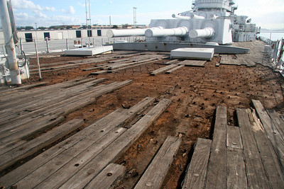 DETAILED VIEW - Work on removing IOWA's forward teak wood deck has begun. The rust will be water- pressure blasted and repainted before the deck wood planking is replaced.