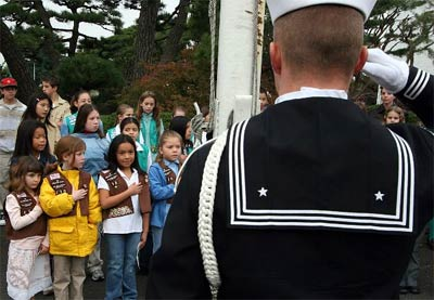 Four Brownie Girl Scouts render honors as Builder Constructionman Jason Bowman salutes during the raising of colors as part of the Naval Air Facility Atsugi Veterans Day observance.