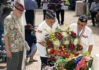 Wreath Greeter, Al Frumkin, left, stands by as members from the Korean War Veterans Association Aloha Chapter presents a wreath in honor of veterans at the National Memorial Cemetery of the Pacific during the Disabled American Veterans 55th Annual Massing of the Colors Veterans Day ceremony.