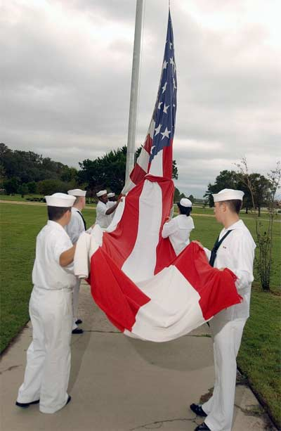 """Sailors prepare to raise the national ensign """"Old Glory"""" during morning colors, at the start of Veterans Day celebrations held aboard the station."""