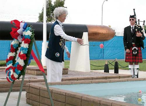 The wife of a World War II U.S. submarine veteran, tosses a flower into a reflecting pool to honor the memory of one of the 52 submarines lost during World War II at the National Submarine Memorial-West on board Naval Weapons Station Seal Beach, Calif. On this Veterans Day, the Submarine Veterans of World War II transferred ownership of the memorial to the U.S. Navy.