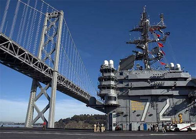 The Nimitz-class aircraft carrier USS Abraham Lincoln (CVN 72) navigates under the Bay Bridge, after a weekend of liberty and Veterans Day celebrations in the port of San Francisco.