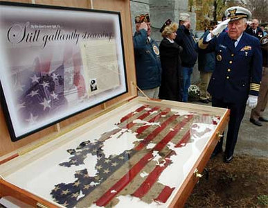Retired Reservist CAPT Ed Bryant, right, salutes during a Veteran's Day gathering at the War Memorial in Ispwich, Mass., Nov. 11, 2003.  A flag from a D-Day landing craft on Omaha Beach in 1944, at left, was displayed during the ceremony.