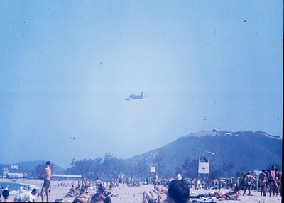 Recreation beach at Nha Trang.  A-1 Skyraider taking off from AF Base.