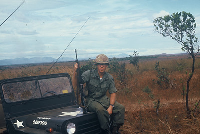 SP4 Fred J Freketic and HQ4 outside Camp Enari and an unloaded M-16.