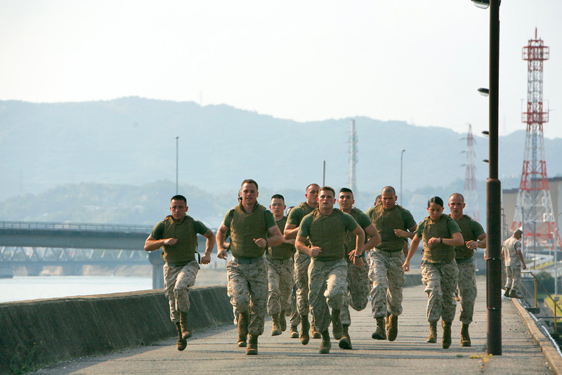 Competitors in the Super Physical Fitness Test take off for a three-mile run while wearing flak jackets and the combat utility uniform on the seawall here June 17. The race, put on by Headquarters and Headquarters Squadron, aimed to find the Marine with the most physical and mental stamina for a chance to ride in the backseat of an F/A-18 fighter jet in an upcoming deployment.