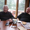 Tom Sexton Jr., 87, of Tewksbury, and his son Tom Sexton III, 58, of Hingham, with WWI memorabilia of Tom Sexton Sr., a US Army private in WWI. They plan to visit areas in France where he served.  The piece of shrapnel on the table was removed from Tom Sr.'s back during the war. (SUN/Julia Malakie)