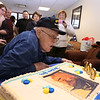 Gayle Gilbert, a WWII Navy veteran who lives at the Bedford VA and turns 100 on February 5, blows out the candles on his cake as he celebrates with family, friends and staff. (SUN/Julia Malakie)