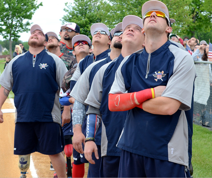 Members of the Wounded Warrior Amputee Softball Team look to the skies as Double amputee parachuter Dana Bowman,United States Army SFC retired, arrives for the Grand Ceremonies of the teams games against the Telford and Souderton Fire Companies,Montco Police and the Telford VFW  at Franconia Park on Saturday May 24,2014. Photo by Mark C Psoras/The Reporter