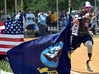 A Wounded Warrior Amputee Softball Team member is seen past a display of flags as he hustles twoards first on a hit during the WWAST game against the Telford Fire Company at Franconia Park on Saturday May 24,2014. Photo by Mark C Psoras/The Reporter