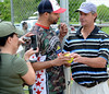 Former Phillies pitcher Jamie Moyer (R) signs a ball for Wounded Warrior Amputee Softball Team  member Axel Alicea during the Grand Ceremonies of the WWAST games against the Telford and Souderton Fire Companies,Montco Police and the Telford VFW at Franconia Park .Moyer threw out the first pitch of the contests on Saturday May 24,2014. Photo by Mark C Psoras/The Reporter