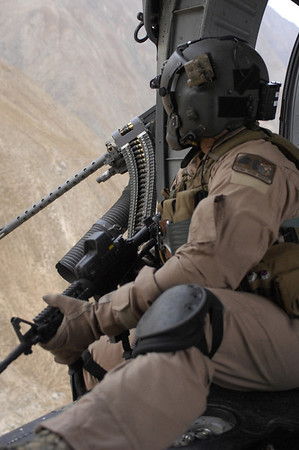 "An arial gunner for an HH-60G Pave Hawk sits behind his M2 .50 caliber machine gun  during a flight. This soldier is deployed with the 33rd Expeditionary Rescue Squadron from Kadena Air Base, Japan, and his job is to protect servicemembers on the ground  providing aid to injured people. He loves his job because it allows him handle ""many kinds of cool gadgets."""