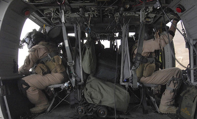 An arial gunner (left), and flight engineer (right), watch the ground while patroling the skies in Afghanistan in an HH-60G Pave Hawk. Both are deployed from Kadena Air Base, Japan.