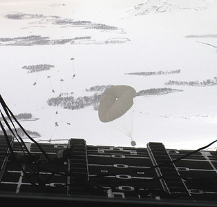 OVER AFGHANISTAN -- Humanitarian supplies drop from the back of a C-130 Hercules.