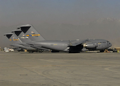 Three C-17 Globemaster IIIs sit on the flightline waiting to be refueled and loaded with cargo.  The C-17's carry large amounts of supplies for airdrops and re-supply missions.  The aircraft can also be used to transport medical patients.  Two of the C-17s are deployed from Charleston Air Force Base, S.C.  The other aircraft is deployed from Travis AFB, Calif.
