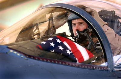 "With three American flags on board his F-15 Eagle, this pilot prepares for a mission.  ""I have two in the front of the canopy to represent my two kids and I carry one on me for my wife,"""