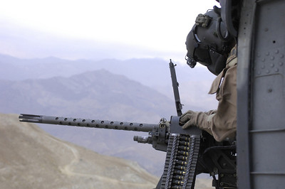 "The ""gunner"" leans out to check the M2 .50 caliber machine gun  mounted on an HH-60G Pave Hawk while flying in Afghanistan. He is currently stationed at Kadena Air Base, Japan."