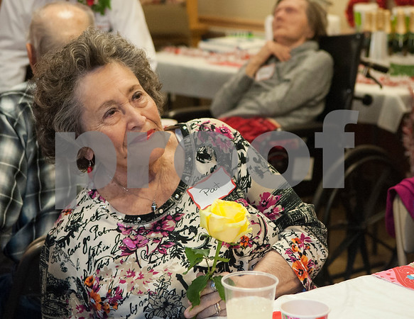 Pat Schneider holds a yellow rose while attending the Watkins-Logan Texas State Veterans Home Sweetheart Luncheon with her husband veteran Jesse Schneider (not pictured) Friday Feb. 12, 2016.   (Sarah A. Miller/Tyler Morning Telegraph)