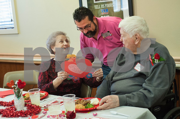 Edgar Hernandez, the assistant director of nurses, visits with resident Glen Milham and his wife Jamie Milham during the Watkins-Logan Texas State Veterans Home Sweetheart Luncheon Friday Feb. 12, 2016. The Milhams celebrated their 65th Valentine's Day, and Mrs. Milham brought a heart-shaped card her husband made her from their 48th Valentine's Day.  (Sarah A. Miller/Tyler Morning Telegraph)