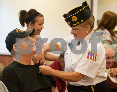 photo by Sarah A. Miller/Tyler Morning Telegraph  Linda Reed of the American Legion Post 474 pins a boutonniere on Vietnam Era United States Army Veteran James Mullen Friday during a recognition ceremony at the Watkins-Logan Texas State Veterans Home in Tyler where he is a resident.