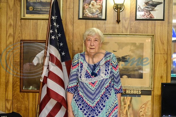 Navy veteran Nancy Martin, who served at the time of the Korean War, stands with the flag while attending the 100th year anniversary of the American Legion Auxiliary. (Jessica T. Payne/Tyler Morning Telegraph)