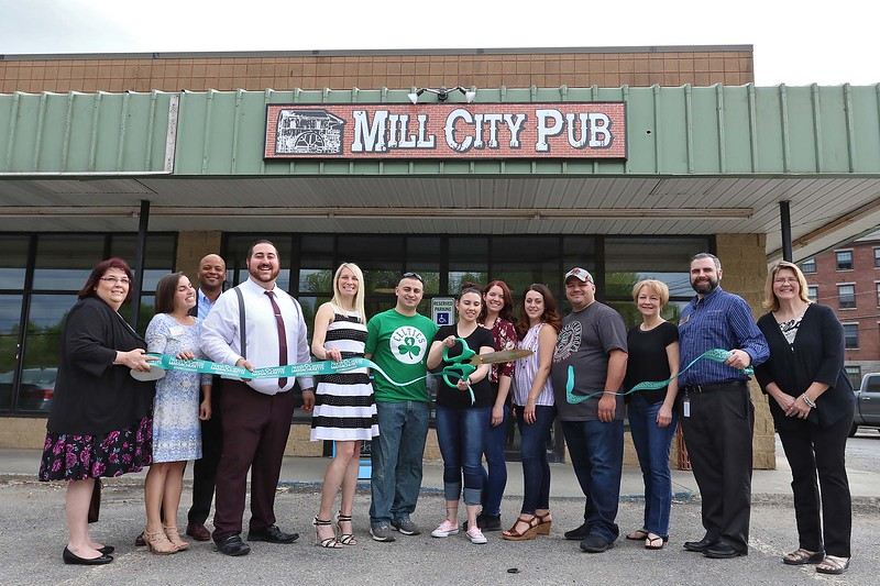Jess Lagoy owner of Mill City Pub in Fitchburg cuts the ribbon to officially open her new place with local officials, member of the chamber and her team from the pub on Thursday afternoon. SENTINEL & ENTERPRISE/JOHN LOVE